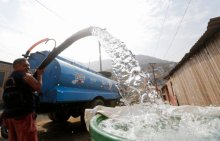 A man delivers water from a water tank in San Juan de Miraflores on the outskirts of Lima