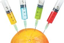 A grapefruit being injected with four syringes containing colour fluids, isolated on white background. Shallow depth of field